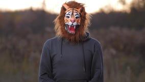 领域,黄色草,日落 下面出现一个人老虎面具的和一件灰色运动衫的 然后他下降下来4K缓慢的Mo 股票视频