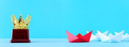 ?? 领导与纸小船的概念图象在蓝色木背景 一位领导引导的othes 库存图片