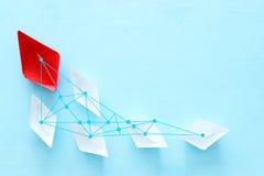 ?? 领导与纸小船的概念图象在蓝色木背景 一位领导引导的othes 免版税图库摄影