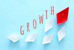 ?? 领导与纸小船的概念图象在蓝色木背景 一位领导引导的othes 库存照片