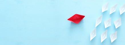 ?? 领导与纸小船的概念图象在蓝色木背景 一位领导引导的othes 免版税库存照片