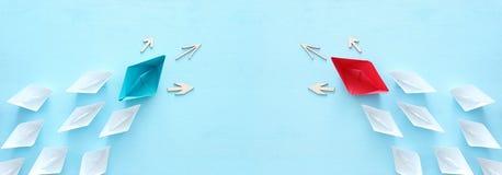 ?? 领导与纸小船的概念图象在蓝色木背景 一位领导引导的othes 免版税库存图片