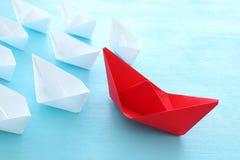 ?? 领导与纸小船的概念图象在蓝色木背景 引导其他的一位领导 库存照片