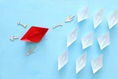 ?? 领导与纸小船的概念图象在蓝色木背景 引导其他的一位领导 免版税图库摄影