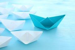 ?? 领导与纸小船的概念图象在蓝色木背景 引导其他的一位领导 库存图片