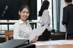 领导女商人概念 微笑在听的确信的年轻亚裔女实业家介绍之间在现代办公室 免版税库存图片