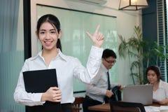 领导女商人概念 有站立反对她的办公室ba的同事的圆环包扎工具的快乐的年轻亚裔女实业家 免版税库存图片