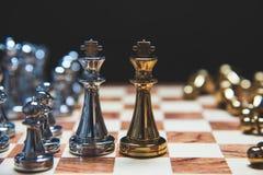 领导战略作为面对的国王的在将死位置的木棋盘 竞争企业营销  库存图片