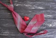 领带,心脏,在装饰木减速火箭的构思设计创造性的言情的背景 免版税库存图片