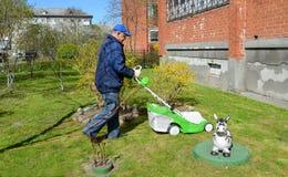 领抚恤金者剪一棵草关于房子的一台割草机 免版税库存照片