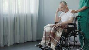 领抚恤金者坐在轮椅的,支持老患者的男性护士在诊所 免版税库存照片