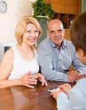 领抚恤金者微笑的成熟夫妇谈话与雇员 免版税库存照片