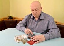 领抚恤金者计数在计算器的金钱 免版税图库摄影
