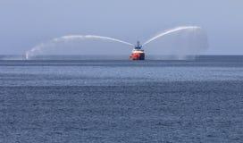 领航船在海湾喷洒的水中 库存图片