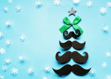 颊须圣诞树,有一把绿色弓和星的,在蓝色背景驱散的雪花,行家的圣诞卡片 库存照片
