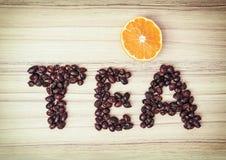 题为茶composited干野玫瑰果用切的桔子 库存照片