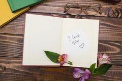 题字'我爱你'在与花,玻璃的一本开放书临近 免版税图库摄影