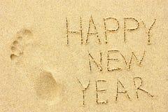题字'新年快乐'和在沙子的人的脚印 免版税库存照片