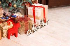 题字'有礼物的新年'和箱子在一根绿色新年的冷杉木附近和与他们一起红色马 图库摄影