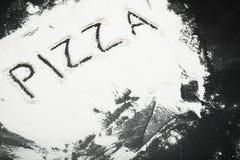 题字'比萨'在桌上用面粉 库存照片