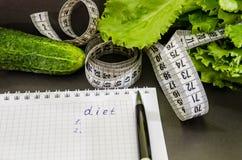 题字'饮食'在一个笔记本、美元、硬币和菜在桌上 免版税库存照片