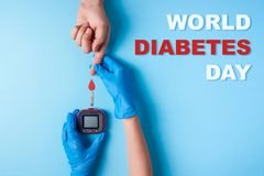题字世界糖尿病天,做有红色血液的护士一只验血人` s手滴下和葡萄糖米 图库摄影