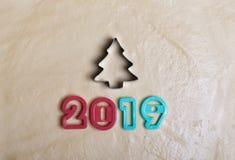 题字以2019年的形式和在未加工的面团的圣诞树,由饼干的模子做成 标志  免版税库存照片