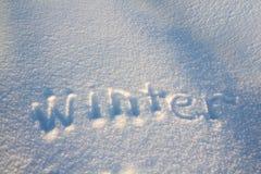 题字冬天,手写在白色新鲜的雪 库存照片