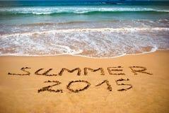 题字在湿沙子夏天2015年 暑假概念照片 库存照片