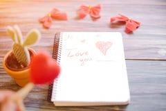 题字我爱你在木背景的一个白色笔记薄 库存照片