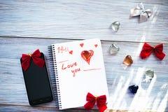 题字我爱你在木背景的一个白色笔记薄 免版税库存图片