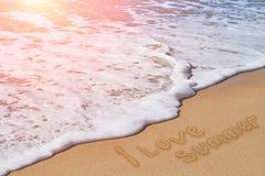 题字我爱在沙子海滩的夏天 免版税图库摄影