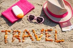 题字旅行、辅助部件晒日光浴的和护照与货币欧洲在沙子在海滩,夏时概念 库存图片