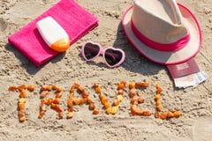题字旅行、辅助部件晒日光浴的和护照与货币欧洲在沙子在海滩,夏时 库存图片