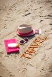 题字旅行、辅助部件晒日光浴的和护照与货币美元在沙子在海滩,夏时 免版税库存图片