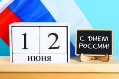 题字是天6月12日,俄罗斯的 在俄罗斯的旗子的背景的木白色日历 免版税库存图片