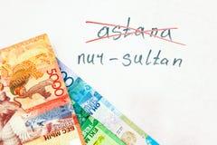 题字注销了阿斯塔纳和努尔苏丹新的名字,与货币的自然白色背景的  图库摄影