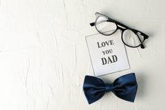 题字爱您爸爸、蓝色蝶形领结和玻璃在白色背景,空间文本的 库存图片