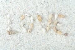 题字爱,由壳做成在沙子 免版税库存图片
