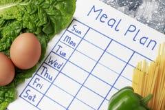 题字膳食计划、日程表在白色板料和沙拉 在视图之上 免版税库存图片