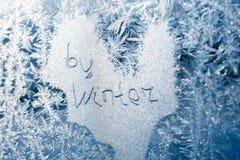 题字:再见,冬天 在冷淡的样式的一个冻冬天窗口 免版税图库摄影