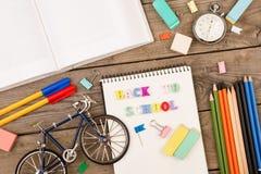 题字& x22; 回到school& x22; 自行车模型、秒表、书、笔记薄和其他文具在棕色木桌上 免版税图库摄影