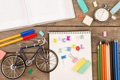 题字& x22; 回到school& x22; 自行车模型、秒表、书、笔记薄和其他文具在棕色木桌上 免版税库存图片
