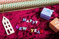 题字& x22; 愉快的新的Year& x22;在天鹅绒背景、圣诞节装饰、礼物盒和包装纸 库存照片