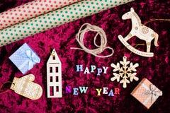 题字& x22; 愉快的新的Year& x22;在天鹅绒背景、圣诞节装饰、礼物盒和包装纸 免版税图库摄影