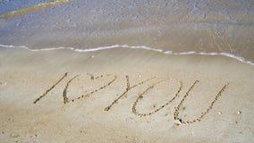 题字& x22; 我爱you& x22;在海附近的沙子 库存照片