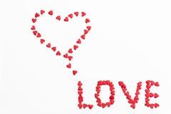 题字`爱`由小心脏做成在白色背景 免版税图库摄影
