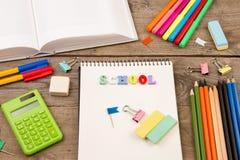 题字& x22; school& x22; 书、计算器、笔记薄和其他文具在棕色木桌上 库存照片