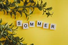 题字sommer用在键盘的信件的德语在黄色背景的与花 免版税库存图片