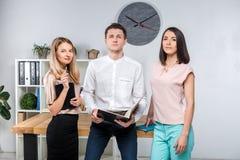 题材事务、配合和合作 一个小组年轻人,三人,立场在桌附近的一个办公室 库存图片